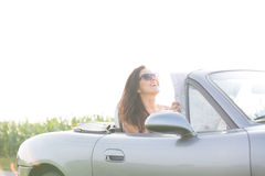Happy woman holding map while sitting in convertible against clear sky Stock Photo