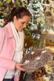 Happy woman holding metallic Christmas wreath Stock Photo