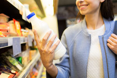 Happy woman holding milk bottle in market. Sale, shopping, consumerism, food and people concept - close up of happy young woman holding milk bottle in market Royalty Free Stock Photography