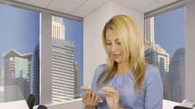 Happy woman holding mobile phone in hand and browsing news in social networks. Adult woman using smartphone on background window with view on skyscrapers in stock footage