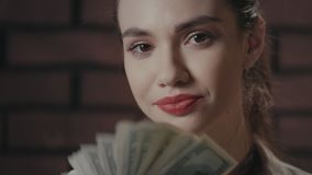 Happy woman holding money in hands looking to camera on brick wall background stock video footage