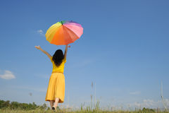 Happy woman holding multicolored umbrella and cloud sky. Relax woman holding multicolored umbrella and blue sky Stock Image