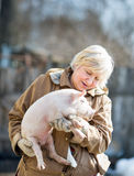 Happy woman holding newborn piglet. Happy woman holding a newborn piglet,domestic animal breeding royalty free stock image