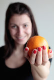 Happy woman holding orange. Happy young woman holds an orange in hand Royalty Free Stock Photos
