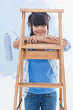 Happy woman holding paint roller leaning on ladder Stock Photography