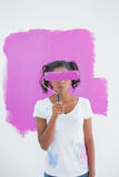 Happy woman holding paintroller over her face. Against pink paint on a wall Stock Photography