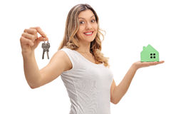 Happy woman holding pair of keys and model house Stock Images