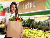 Happy woman holding a paper bag full of fruit and vegetables. Stock Photography