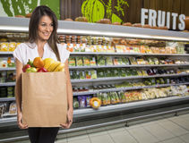 Happy woman holding a paper bag full of fruit and vegetables. Stock Photo