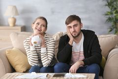 Happy woman holding piggy bank and sad man. Happy women holding piggy bank and sad men with bills at home. Money problems in relationship Royalty Free Stock Photo