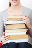 Happy woman holding pile of books Stock Photo