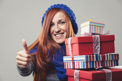 Happy woman holding piled Christmas gifts Royalty Free Stock Image