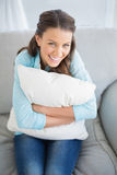 Happy woman holding pillow sitting on couch Stock Images