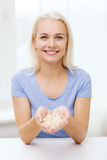 Happy woman holding pills or capsules at home Royalty Free Stock Photos
