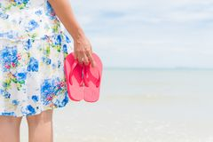 Happy woman holding pink flip flop on sandy beach stock photos