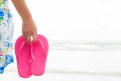 Happy woman holding pink flip flop on sandy beach for summer. Holiday and vacation concept stock photo