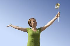Happy Woman Holding Pinwheel Toy Stock Image