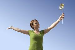 Happy Woman Holding Pinwheel Toy Stock Image