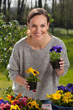 Happy woman holding pots with pansy flowers Royalty Free Stock Photography