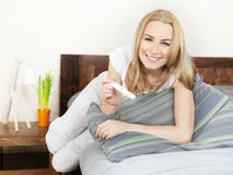 Happy woman holding pregnancy test stock photography