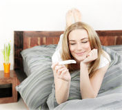 Happy woman holding pregnancy test stock photos