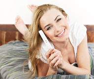 Happy woman holding pregnancy test royalty free stock photos