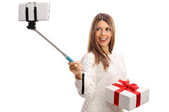 Happy woman holding present and taking selfie with a stick Royalty Free Stock Photography
