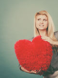 Happy woman holding red pillow in heart shape Stock Photos