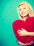 Happy woman holding red pillow in heart shape Royalty Free Stock Photography
