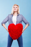 Happy woman holding red pillow in heart shape Royalty Free Stock Image