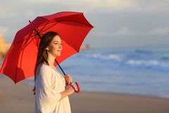 Happy woman holding umbrella contemplating the ocean. Happy woman holding red umbrella contemplating the ocean walking on the beach stock photography