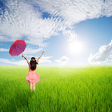 Happy Woman holding red umbrella in green rice fields in sun sky Stock Photo