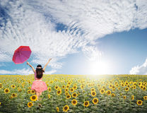 Happy woman holding red umbrella in sunflower field and blue sky Stock Photo