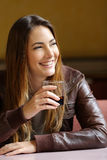 Happy woman holding a refreshment in a restaurant. Happy woman thinking and holding a refreshment in a restaurant stock images