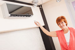 Happy woman holding a remote control air conditioner Royalty Free Stock Photo