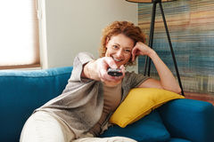 Happy woman holding remote control lying on cozy couch Stock Photo