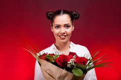 Happy woman holding a roses bouquet in hands smiling at camera Royalty Free Stock Image