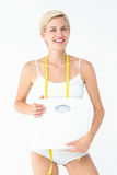 Happy woman holding scales smiling at camera Stock Photos