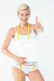 Happy woman holding scales with thumbs up Royalty Free Stock Images