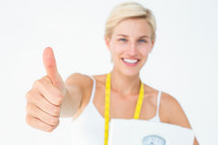 Happy woman holding scales with thumbs up Royalty Free Stock Photos