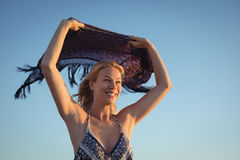 Happy woman holding scarf against clear sky Stock Photo