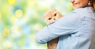 Happy woman holding scottish fold cat over green Royalty Free Stock Photos