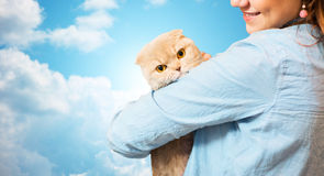 Happy woman holding scottish fold cat over sky Royalty Free Stock Images