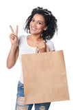 Happy woman holding shopping bag with empty copy space and gesturing V sign Royalty Free Stock Image