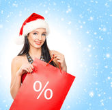 Happy woman holding a shopping bag on the snow Royalty Free Stock Photos