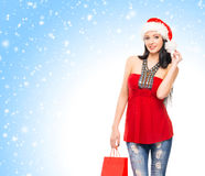 Happy woman holding a shopping bag on the snow Stock Image