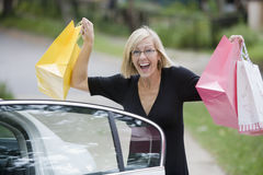 Happy woman holding shopping bags Stock Photos