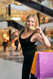Happy woman holding shopping bags and credit card Royalty Free Stock Photos