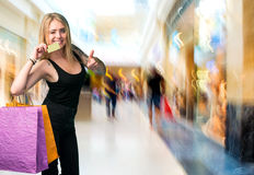 Happy woman holding shopping bags and credit card Royalty Free Stock Images