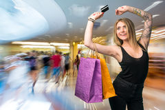 Happy woman holding shopping bags and credit card Stock Image